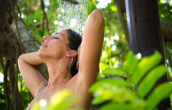 Relaxed happy woman taking spa shower outdoor in exotic garden.